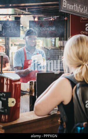 London, UK - September 17, 2018: Woman waiting for her food at Northfield Butchery stand in Borough Market, staff cooking on the background. Borough M - Stock Photo