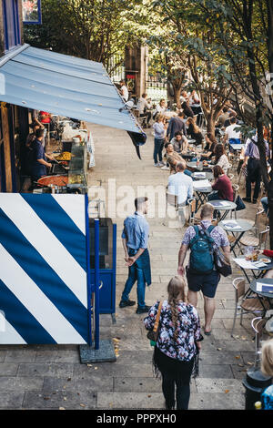 London, UK - September 17, 2018: People sitting at tables and walking past market stalls in Borough Market, one of the largest and oldest food markets - Stock Photo