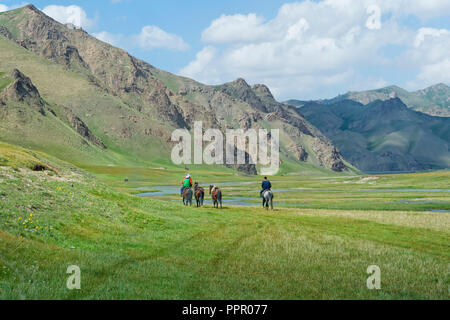 Horsemen riding in Kurumduk valley, Naryn province, Kyrgyzstan, Central Asia - Stock Photo