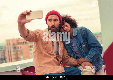 Playful young couple making silly faces while taking selfies - Stock Photo