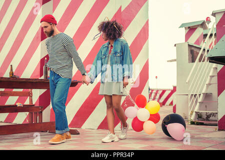 Exhausted couple walking on the roof after night party and looking sleepy - Stock Photo