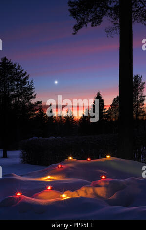 Christmas Star in winter sky at dusk. Candle lanterns glowing in the snow. - Stock Photo