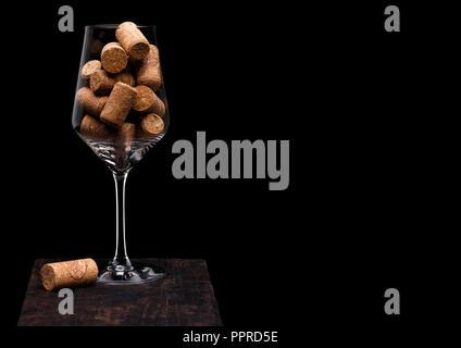 Wine glass with corks inside with cork next to glass on wooden board on black - Stock Photo