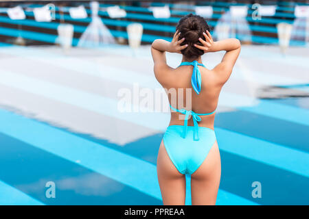 back view of tanned girl posing in blue bikini near swimming pool - Stock Photo