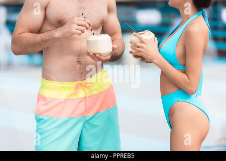 cropped view of young couple holding coconut cocktails with straws - Stock Photo