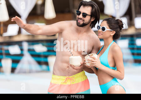 young couple in sunglasses with coconut cocktails, man showing something - Stock Photo
