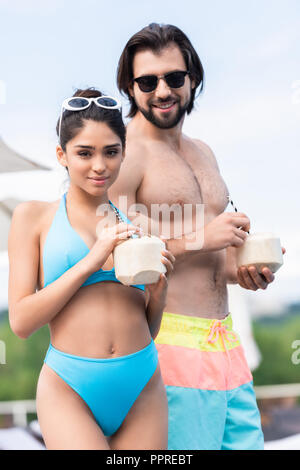 young beautiful couple in sunglasses holding coconut cocktails - Stock Photo