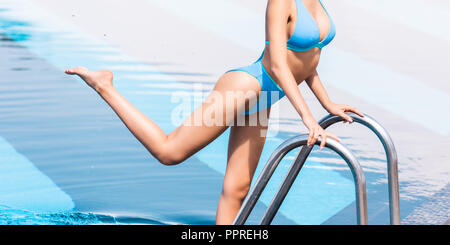 cropped view of tanned girl in bikini posing on ladder in swimming pool - Stock Photo