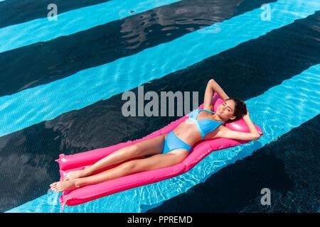 young woman in bikini lying on pink inflatable mattress in swimming pool - Stock Photo