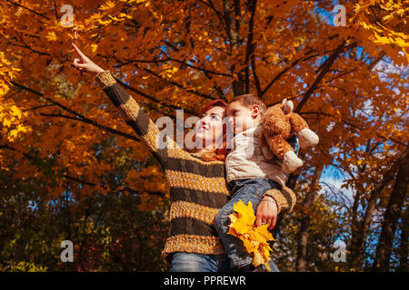Happy mother and her little son walking and having fun in autumn forest. Woman showing something to her kid - Stock Photo