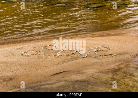 The word 'Love' written in stones on a sandy beach, White Mountain National Forest, NH - Stock Photo