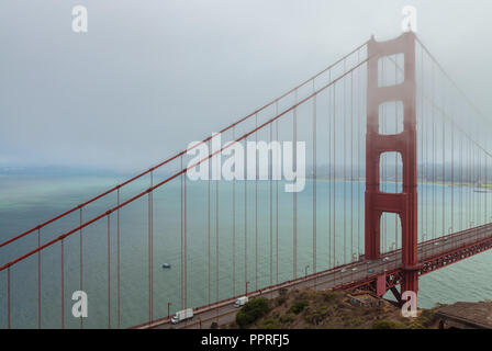 The iconic Golden Gate Bridge partially covers with fog, San Francisco, California, United States. - Stock Photo