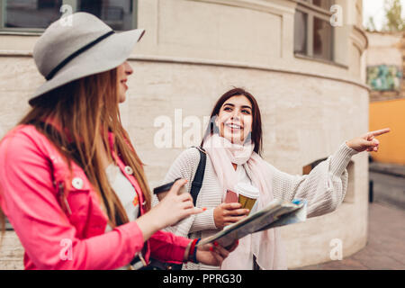 Two women tourists searching for right way using map on city street. Happy friends travelers pointing on direction - Stock Photo