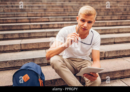 College student with backpack using tablet sitting on stairs and holding glasses. Guy studying outdoors. Education concept - Stock Photo