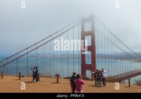 Tourist are taking photographs at the iconic Golden Gate Bridge partially covers with fog, San Francisco, California, United States. - Stock Photo