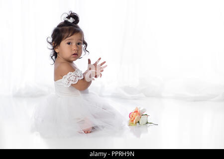 A one year old, baby girl sitting on the floor with a flower. She is wearing a white, tulle dress wtih lace sleeves. - Stock Photo