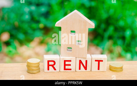 Wooden house, coins with the inscription rent. Rental of property, apartments. services of a realtor. affordable housing, rental prices. real estate - Stock Photo