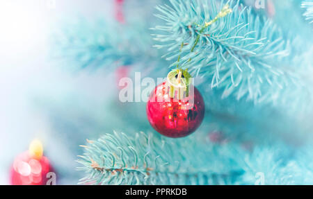 Christmas tree toys decorations and snow-covered Christmas tree branches close-up. Winter Christmas New Year background. - Stock Photo