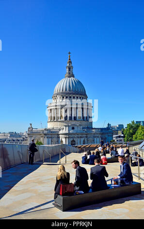 Office workers eating lunch on the roof of One New Change with a view of St Paul's Cathedral, London, England, UK. - Stock Photo