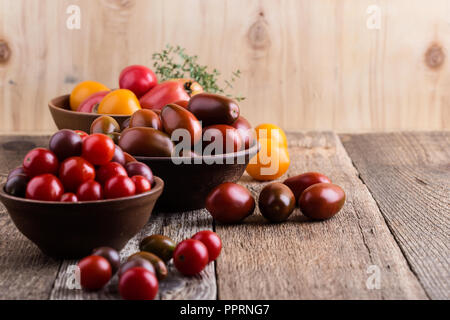 Colorful tomatoes on rural wooden table, autumn harvest time, organic farmer vegetables - Stock Photo