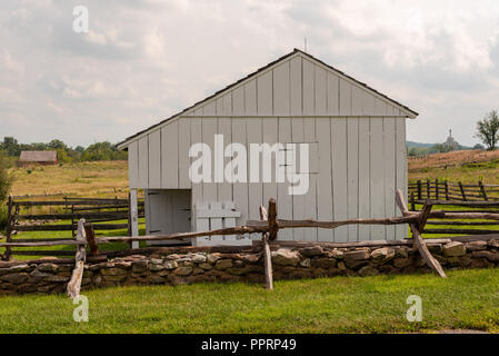 A white barn surrounded by wooden fencing on an historic Gettysburg battlefield. - Stock Photo