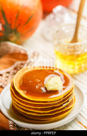 Fresh homemade pumpkin pancake with honey and butter in a white plate. Traditional Tasty healthy Breakfast for gourmets. Selective focus - Stock Photo