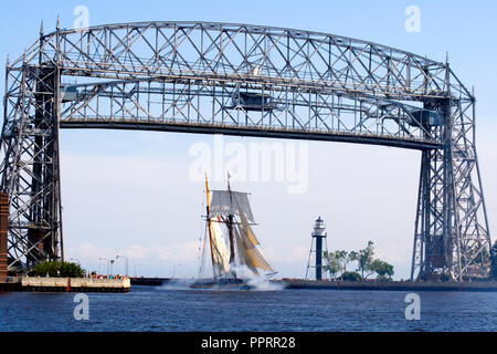 Pride of Baltimore II Tall Ship sailing under the Aerial Lift Bridge in the Duluth Port of Lake Superior Canal Park. Duluth Minnesota MN USA - Stock Photo