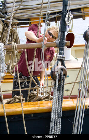 Crew member works on lashing rope on the Tall Ship Pride of Baltimore II moored in the Duluth Port of Lake Superior Duluth Minnesota MN USA - Stock Photo
