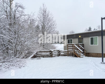 Small yard covered with snow in front of the house on winter day in Canada - Stock Photo