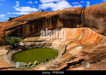 Waterhole also known as gnamma holes by the aboriginals and wave rock formation at Beringbooding Rock Western Australia - Stock Photo