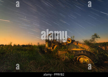 An old Caterpillar Road Grader rusts away in a pasture while star trails and a satellite streak overhead. - Stock Photo