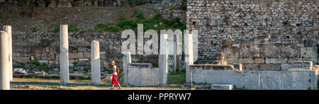 Athens Greece/August 17, 2018:  Tourist with red pants and hat walking through Ancient ruins in Athens - Stock Photo