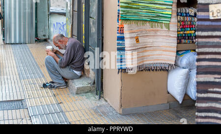 Athens Greece/August 17, 2018: Woman walking down closed down flea market with graffiti on the closed doors - Stock Photo