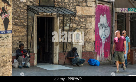 Athens Greece/August 17, 2018: Two homeless men sitting in front of chruch with people walking by - Stock Photo