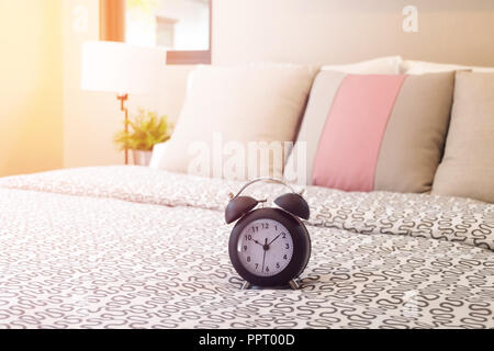 close up of alarm clock on bed with sunlight in bedroom - Stock Photo