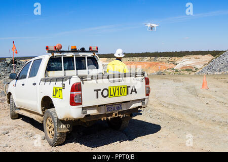 Surveyor using a drone to measure ore stockpile at a gold mine in Western Australia - Stock Photo