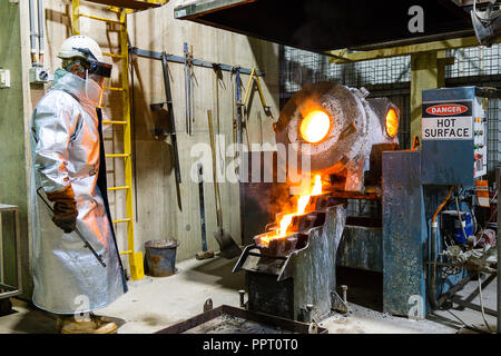 Worker in protective clothing pouring gold from a furnace at a gold mine in Western Australia - Stock Photo
