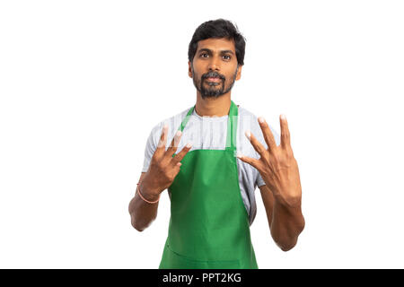 Hypermarket or supermarket indian male employee showing seven sign with both hands by holding fingers up isolated on white studio background - Stock Photo