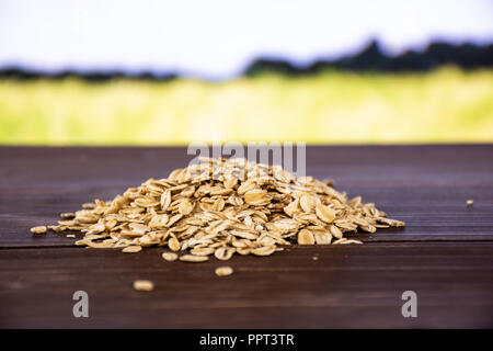 Lot of whole flat raw rolled oats heap with green wheat field in background - Stock Photo