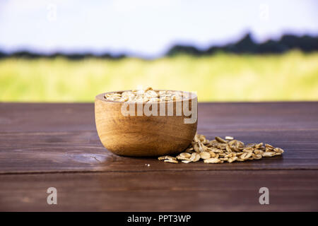 Lot of whole flat raw rolled oats with wooden bowl with green wheat field in background - Stock Photo