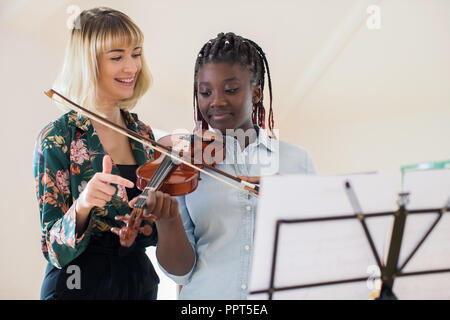 Tutor Teaching High School Student To Play Violin In Music Lesson - Stock Photo