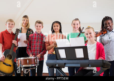 Portrait Of High School Students Playing In School Orchestra With Teacher - Stock Photo
