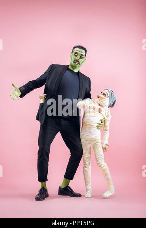 Halloween Family. Happy Father and Children Girl in Halloween Costume and Makeup. Bloody theme: the crazy maniak faces on pink studio background - Stock Photo