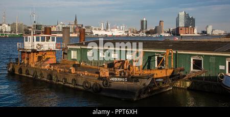 Hamburger Hafen, Arbeitsschiff WASSERBAU I vor Holzbaracke, am Horizont Skyline der Stadt mit Museumsschiff CAP SAN DIEGO und Elbphilharmonie - Stock Photo