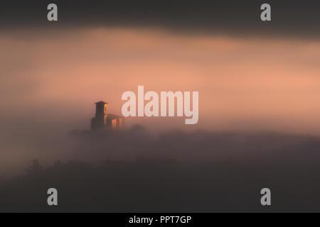 Church in Aramaio surrounding by fog - Stock Photo