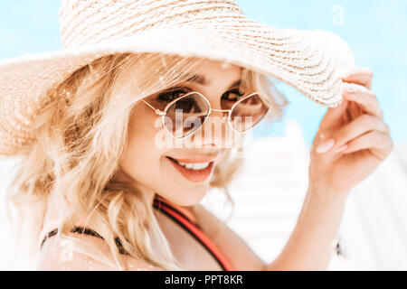 portrait of beautiful young blonde woman in wicker hat and sunglasses smiling at camera near pool - Stock Photo