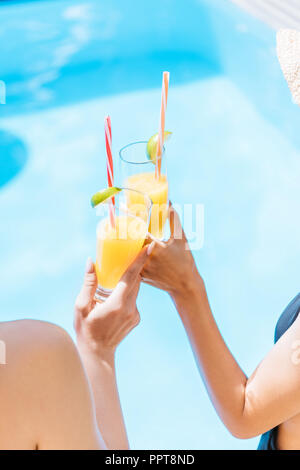 cropped shot of young women in swimwear and hats clinking glasses with refreshing beverages at pool - Stock Photo