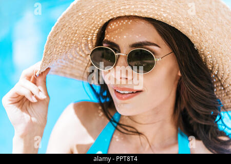 beautiful brunette woman in sunglasses and straw hat smiling at poolside - Stock Photo