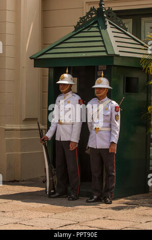 Armed guards in white jackets and white topees on duty at the Grand Palace, Bangkok, Thailand - Stock Photo