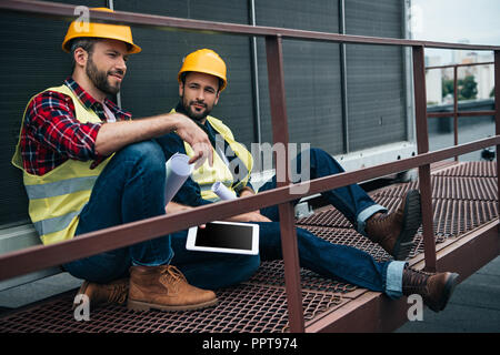 architects in hardhats with blueprints and digital tablet sitting on construction - Stock Photo